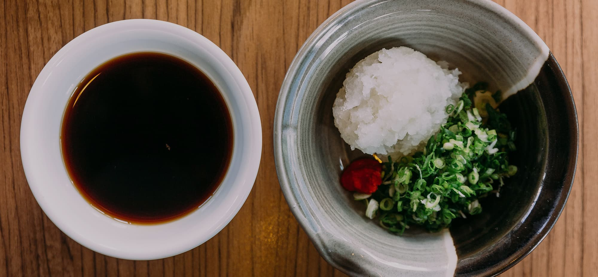 Image of a sauce in a bowl next to a serving of boiled rice