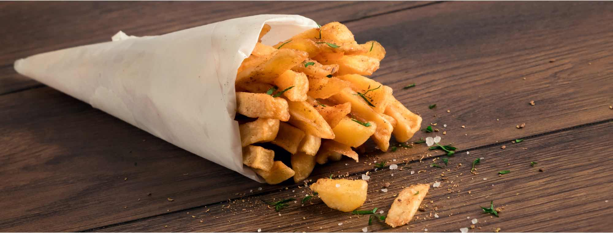 Fresh hot chips are packaged in an open paper bag